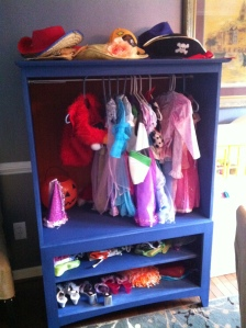 entertainment center filled with childrens dress-up clothing and turned into a closet for children