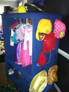 side of dress up closet with hats hung up on side and clothes indie the main part.