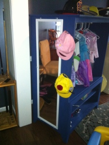 other side of the dress up closet with clothes in the main part, a mounted mirror and hats on the hooks.